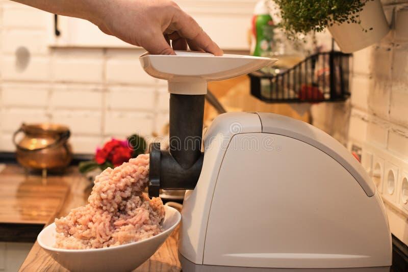 Cozinhando a carne triturada em uma picadora de carne elétrica na mesa de cozinha fotografia de stock royalty free