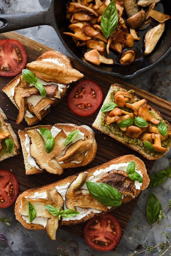Cozinhando cogumelos selvagens da floresta Sanduíches com primas e cogumelos fritados do porcini, tomates e manjericão no fundo e fotos de stock