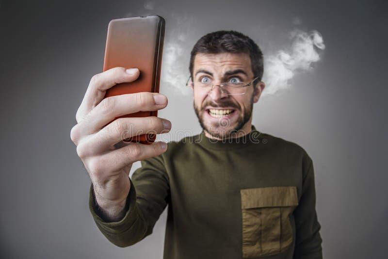 Cozinhando com raiva, homem que grita em seu telefone fotografia de stock