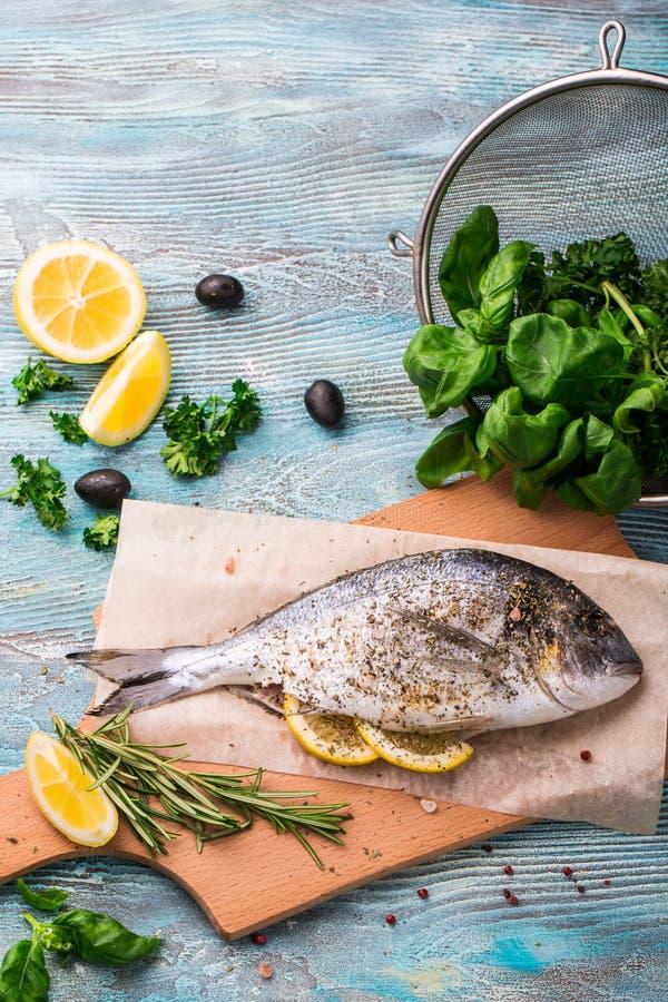 Cozinhando Dorado cru pesque com espinafres, alecrins, azeitonas, close up das ervas, das especiarias e do limão na placa de cort imagens de stock
