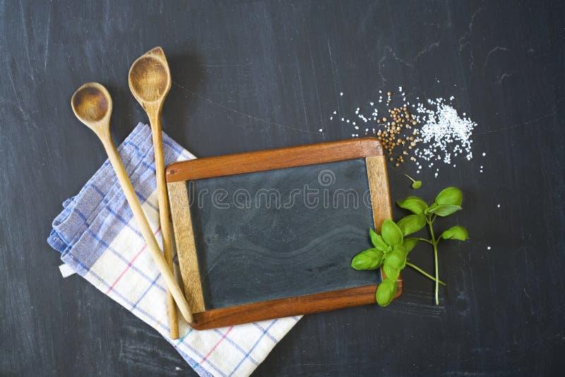 Cozinhando ingredientes e utensílios, espaço da cópia gratuita na placa do preto da cozinha da placa fotos de stock royalty free