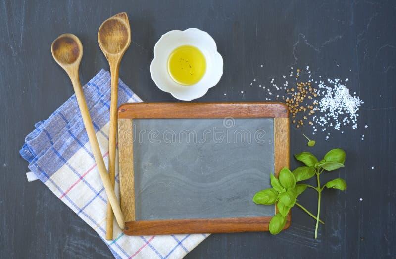 Cozinhando ingredientes e utensílios, espaço da cópia gratuita na placa vazia do preto da cozinha, trocista acima imagem de stock royalty free