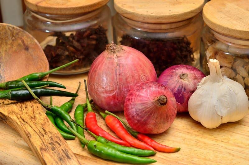 Cozinhando ingredientes Especiaria e ervas com cebola e alho na placa de madeira fotos de stock royalty free
