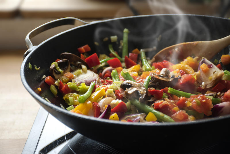 Cozinhando legumes misturados no frigideira chinesa, estilo asiático que cozinha o vegeta imagens de stock