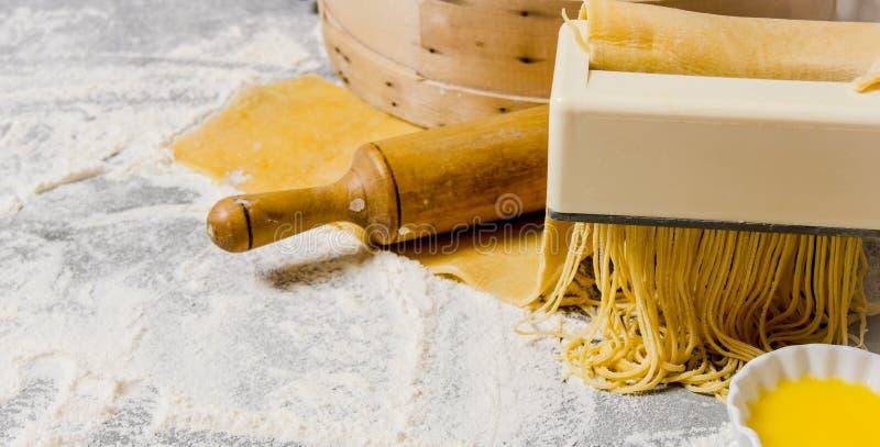 Cozinhando macarronetes O fabricante da massa com um pino e um ovo do rolo imagens de stock royalty free