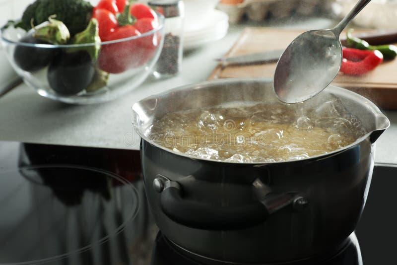 Cozinhando a massa no potenciômetro no fogão elétrico imagem de stock