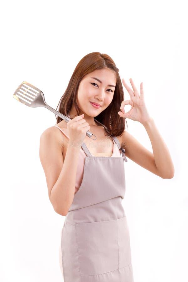 Cozinhando a mulher que dá o sinal aprovado da mão a você, branco isolado foto de stock