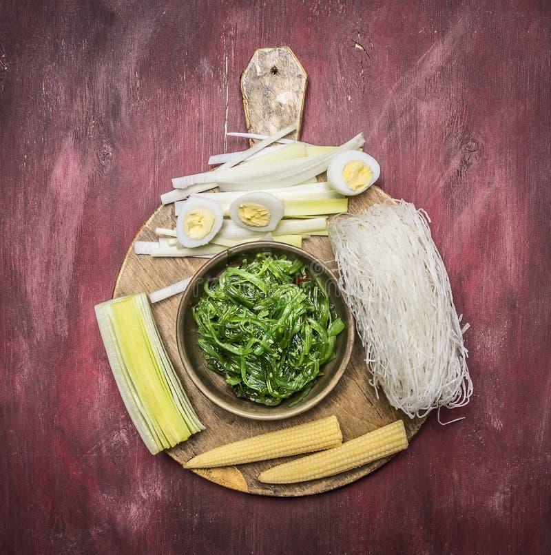 Cozinhando o alimento coreano, os macarronetes de vidro, alga do chuka, ferveram ovos de codorniz, gengibre, milho em um fundo rú imagem de stock