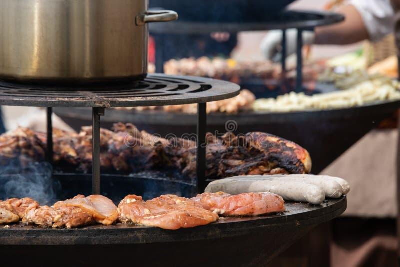 Cozinhando o alimento da rua - carne, aves domésticas e salsichas em um soldador redondo imagem de stock royalty free