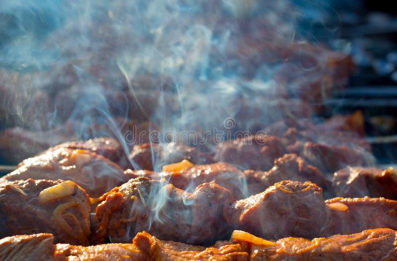 Cozinhando o assado na grade com fumo Cozinhe a carne posta de conserva fresca com cebolas O assado posto de conserva grade é pre foto de stock royalty free