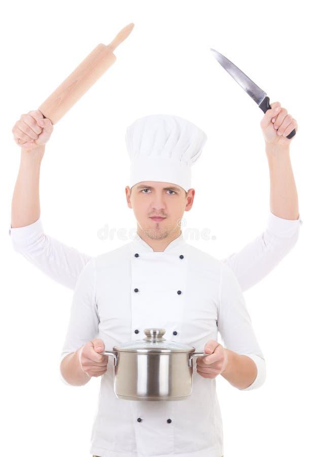 Cozinhando o conceito - homem novo no uniforme do cozinheiro chefe com as quatro mãos que guardam o equipamento da cozinha fotografia de stock