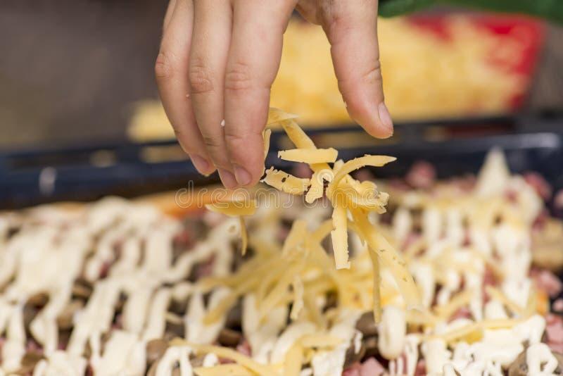 Cozinhando o conceito - mão do cozinheiro que adiciona o queijo raspado à pizza na pizaria Especiarias de derramamento da mão do  foto de stock
