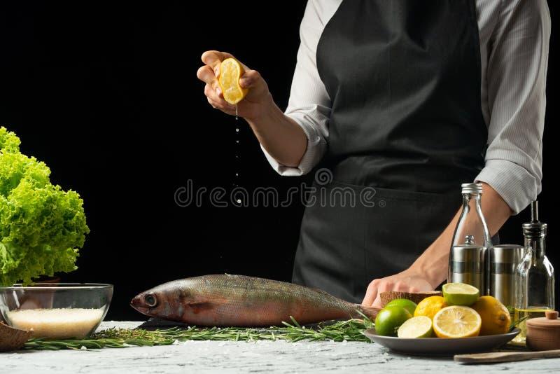 cozinhando o cozinheiro chefe de peixes frescos, o cozinheiro chefe derrama o suco de limão em um fundo preto com o uso do snazma foto de stock