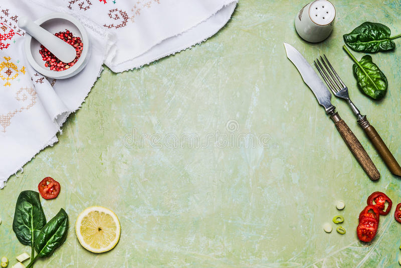 Cozinhando o fundo com cutelaria, as ervas, as especiarias, o almofariz e o pilão rústicos no fundo de madeira chique gasto verde fotos de stock