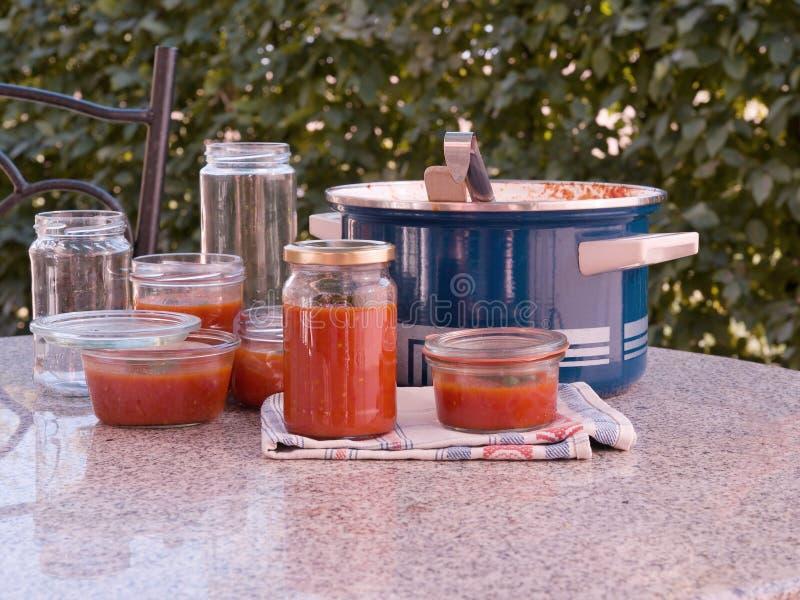 Cozinhando o molho de tomate caseiro do estilo italiano e preservating nos frascos preservating no jardim fotografia de stock royalty free