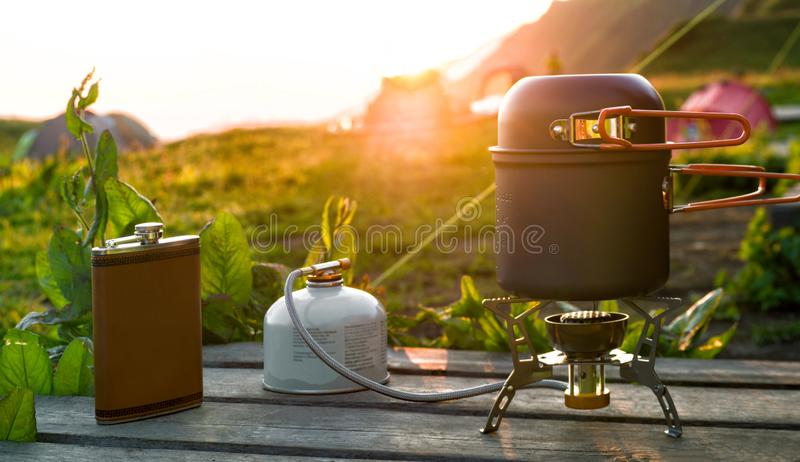Cozinhando o potenciômetro no fogão de gás de acampamento e na garrafa anca imagens de stock royalty free