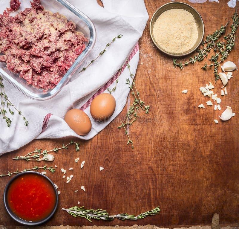 Cozinhando o prato da carne crua com côdeas de pão ralado e do molho de tomate dos ovos com alho e fundo de madeira rústico do gu imagens de stock