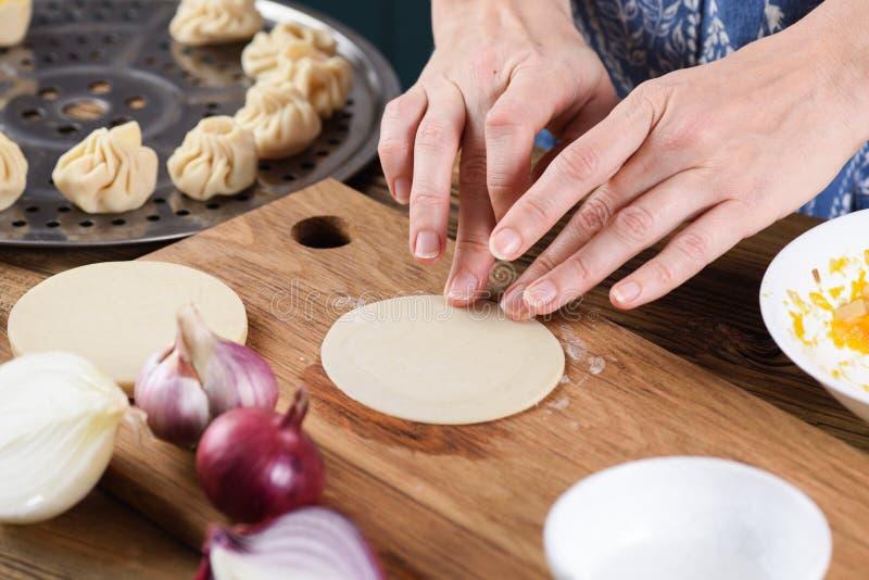 Cozinhando o prato de vegetariano saudável Mãos da mulher que fazem o dumpli do vapor fotografia de stock royalty free