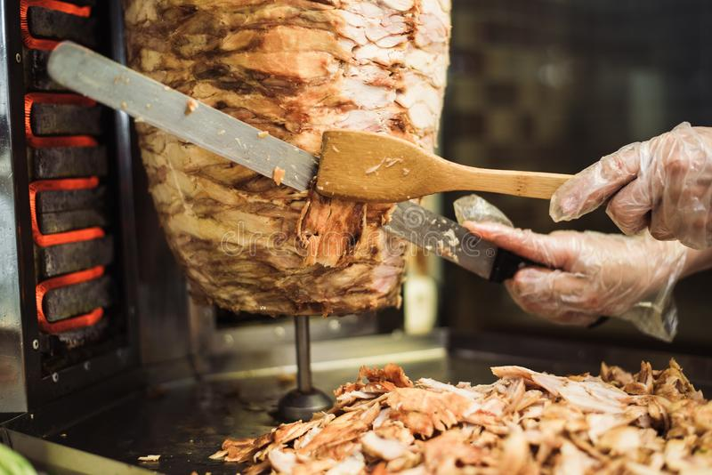 Cozinhando o shawarma e o ciabatta em um café Um homem na carne dos cortes das luvas descartáveis em um espeto imagens de stock