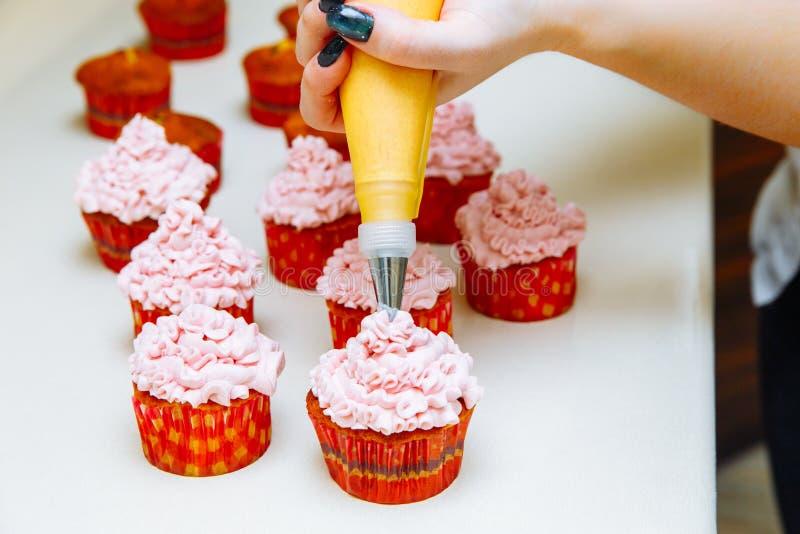 Cozinhando queques em casa Decoração de cozimento de creme do rosa fotografia de stock royalty free