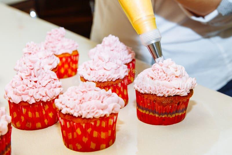 Cozinhando queques em casa Decoração de cozimento de creme do rosa imagem de stock