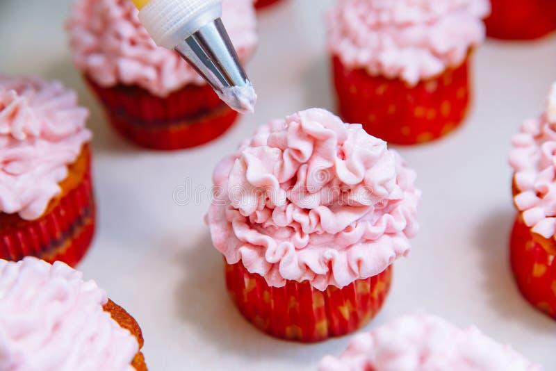 Cozinhando queques em casa Decoração de cozimento de creme do rosa fotos de stock royalty free