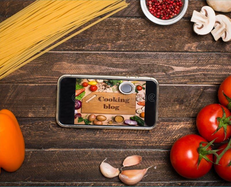 Cozinhando receitas em linha: cozinhando o blogue em uma tela do smartphone, ing fotografia de stock royalty free