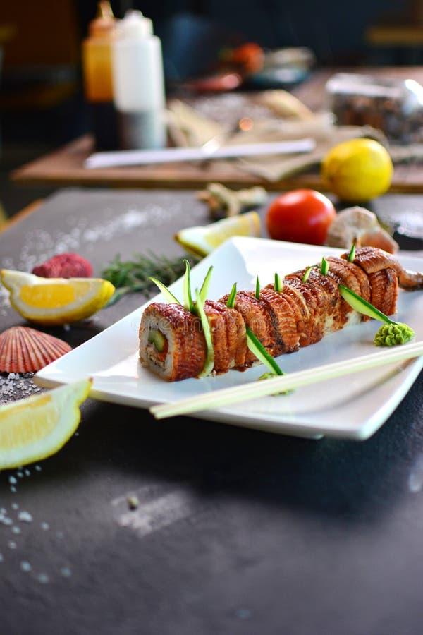 Cozinhando rolos e o sushi japoneses foto de stock