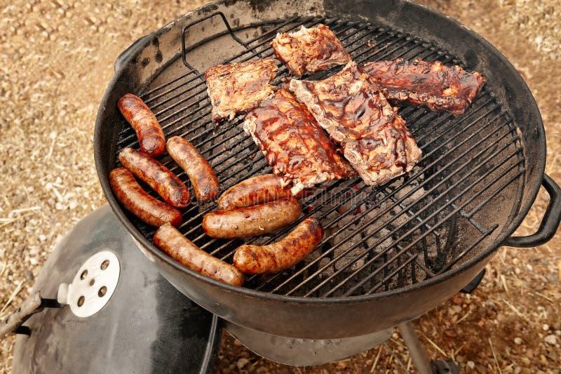 Cozinhando salsichas e cremalheiras dos reforços fora em uma grade abastecida carvão vegetal imagens de stock