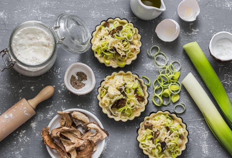 Cozinhando a segurelha do vegetariano entrega a torta com cogumelos do porcini, alho-porros, batatas e rúcula, salada dos tomates imagens de stock