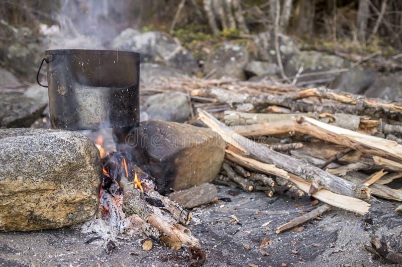 Cozinhar com um jogador que esteja em duas pedras e em uma fogueira seja imagens de stock