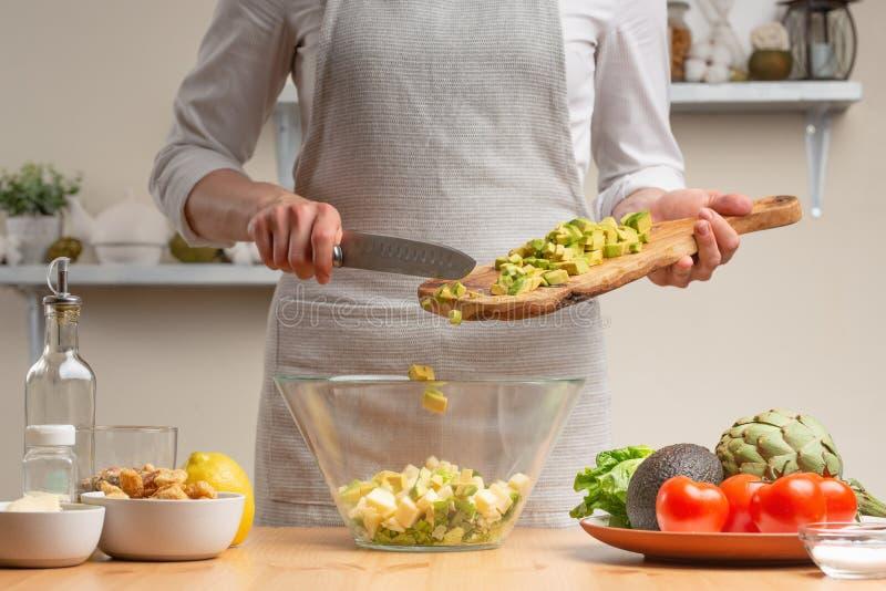 cozinhar O cozinheiro chefe derrama o abacate, em processo de uma salada do vegetariano na cozinha da casa Fundo claro Menu do re fotos de stock royalty free