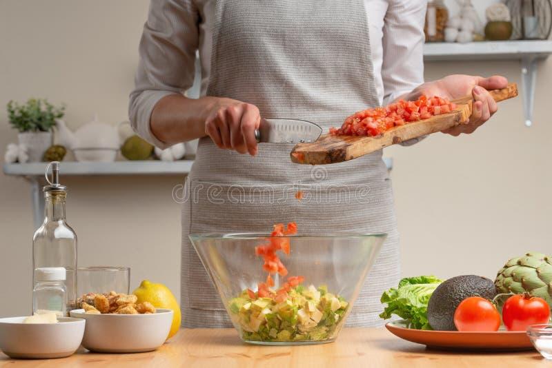 cozinhar O cozinheiro chefe derrama tomates, em processo da salada do vegetariano na cozinha da casa Fundo claro Menu do restaura imagem de stock