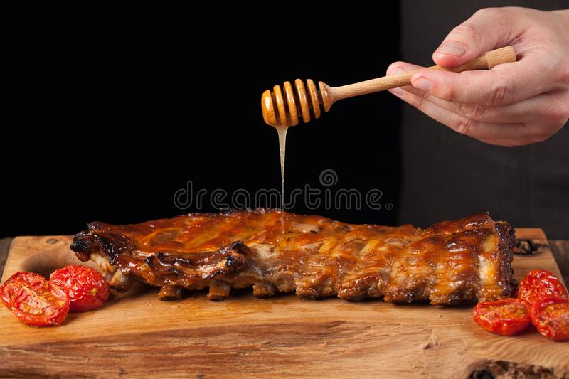 Cozinhar o reforço de carne de porco desbasta com molho doce do mel no fundo de madeira escuro O cozinheiro chefe derrama reforço foto de stock