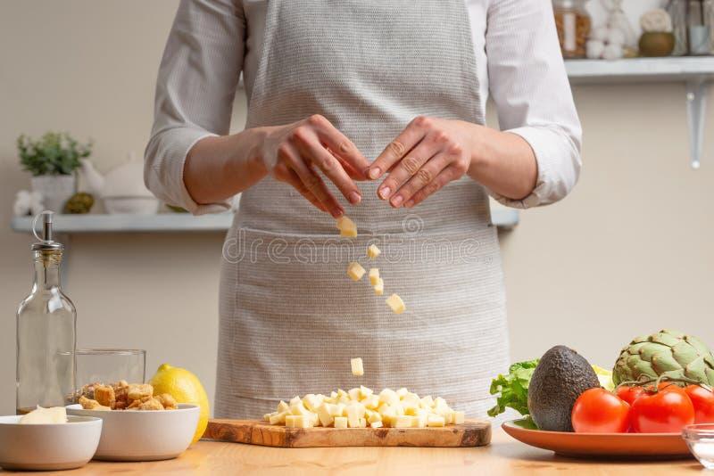 cozinhar Um cozinheiro chefe derrama o queijo da mussarela ou de feta, em processo de uma salada do vegetariano na cozinha da cas fotografia de stock