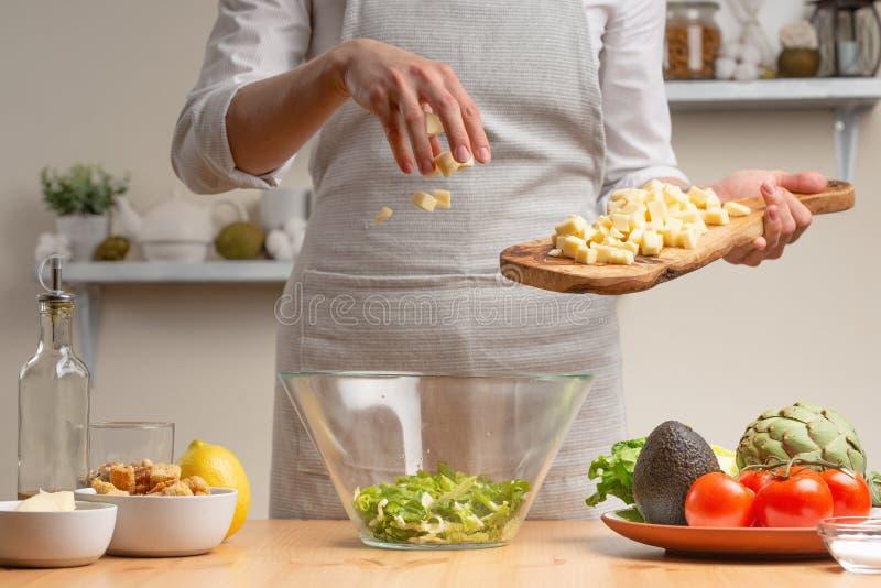 cozinhar Um cozinheiro chefe derrama o queijo da mussarela ou de feta, em processo de uma salada do vegetariano na cozinha da cas imagem de stock royalty free