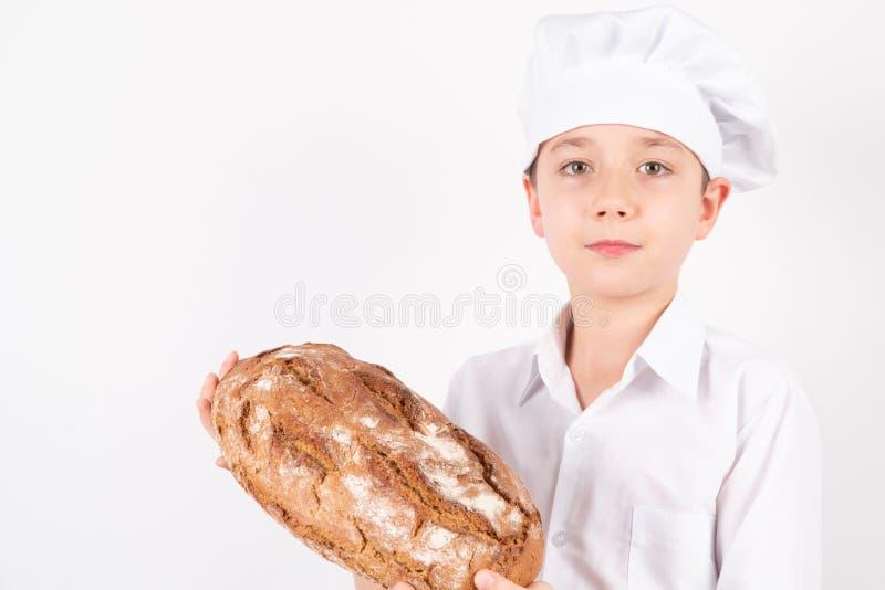 Cozinhe Boy With Bread no fundo branco fotos de stock royalty free