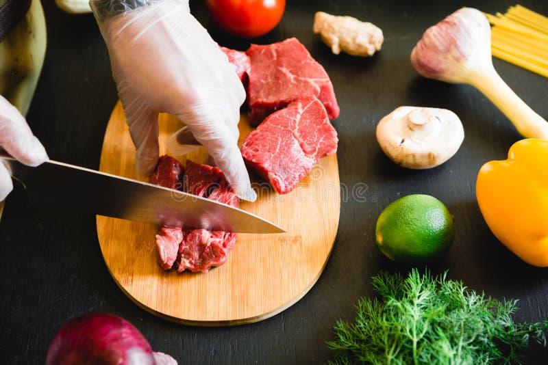 Cozinhe a carne do corte em uma placa de madeira e em uns vegetais crus frescos na tabela escura imagens de stock