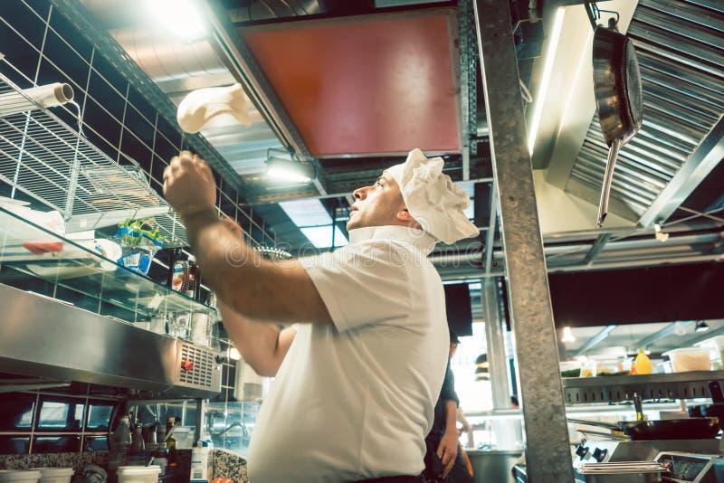 Cozinhe lanç a massa ao preparar a pizza em um restaurante italiano moderno fotografia de stock royalty free