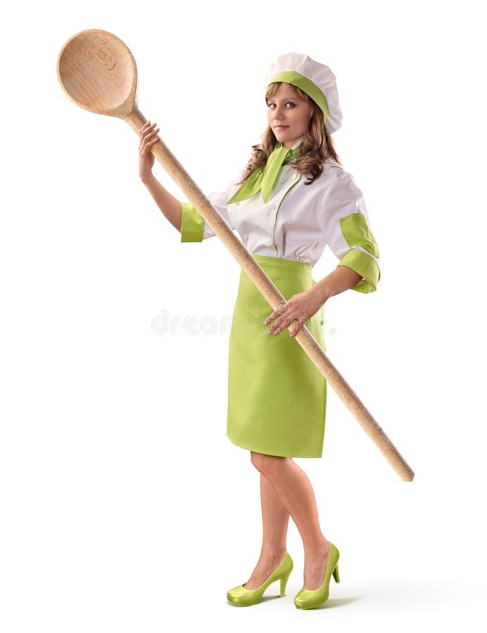 Cozinhe a menina do cozinheiro chefe com uma colher de madeira grande no backgro isolado branco foto de stock royalty free
