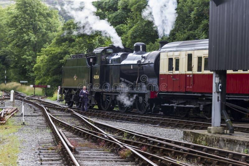 Cozinhe o trem nos tapumes na estação de trem em Keighley e em estrada de ferro do vale do valor Yorkshire, Inglaterra, Reino Uni fotos de stock royalty free