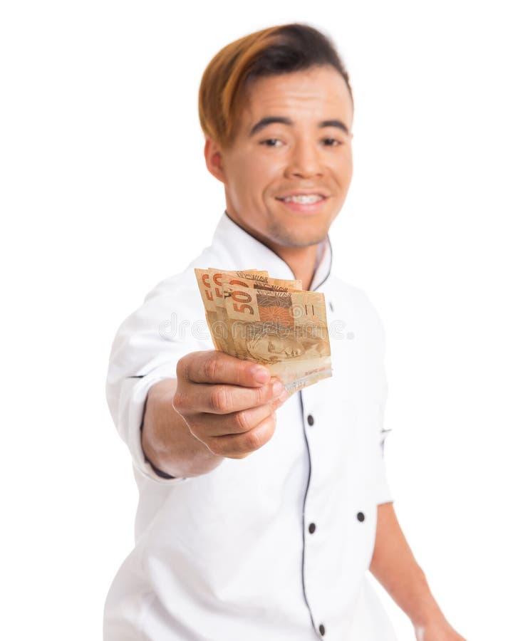 Cozinhe o uniforme vestindo do trabalho e mostrar contas do dinheiro fotos de stock
