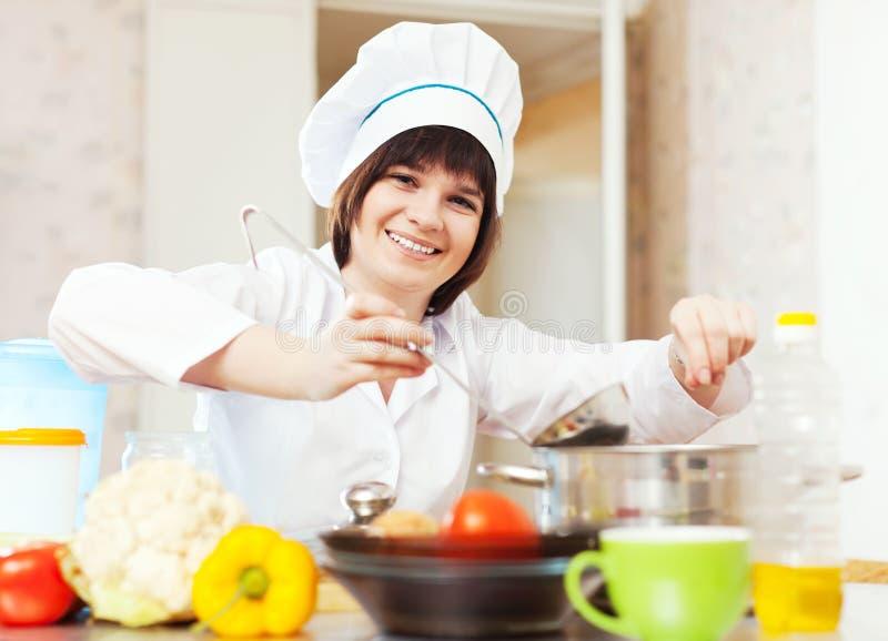 Cozinheiro   adiciona o sal ou as especiarias na sopa fotos de stock
