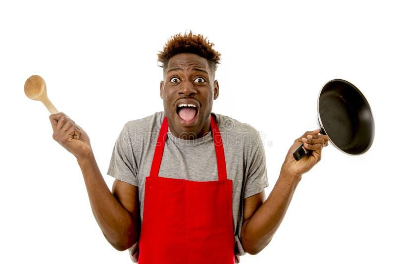 Cozinheiro afro-americano preto da casa do homem no avental do cozinheiro chefe que cozinha a bandeja e a colher perdidas e sobre fotografia de stock
