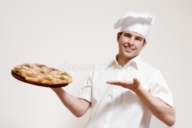 Cozinheiro atrativo feliz com uma pizza nas mãos fotografia de stock