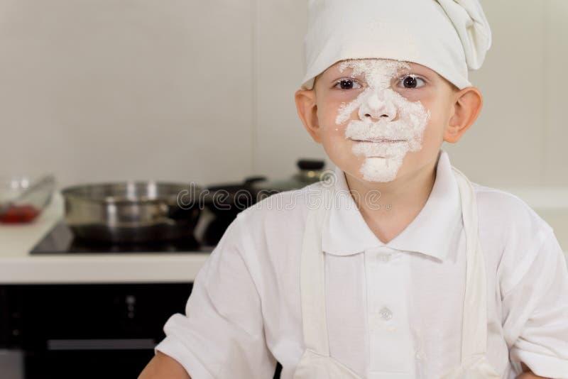 Cozinheiro bonito do rapaz pequeno com uma cara completa da farinha foto de stock