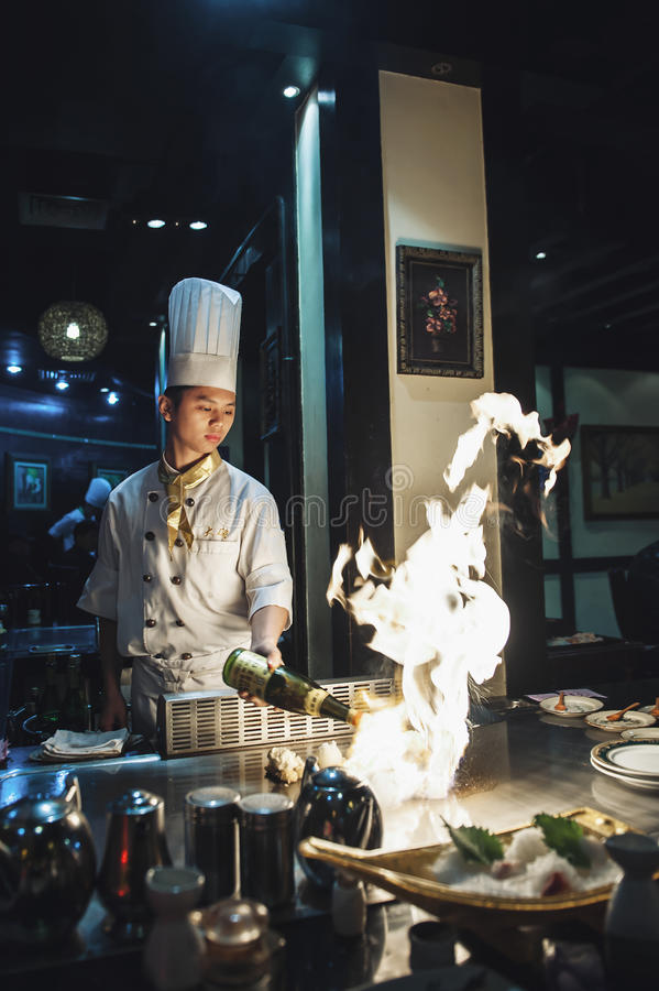 Cozinheiro chefe asiático que faz o cozimento chinês fotografia de stock royalty free