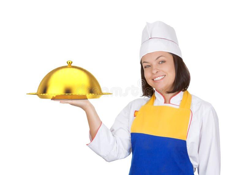 Cozinheiro chefe bonito da jovem mulher com a campânula dourada do restaurante foto de stock royalty free