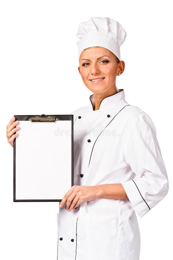 Cozinheiro chefe bonito da mulher do cozinheiro que guardara um quadro de mensagens imagens de stock