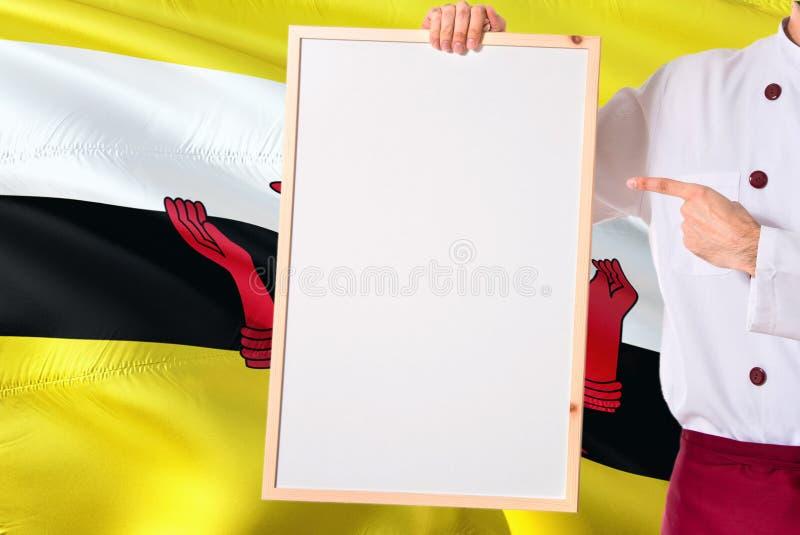 Cozinheiro chefe Bruneian que guarda o menu vazio do whiteboard no fundo da bandeira de Brunei Darussalam Cozinhe o uniforme vest imagem de stock